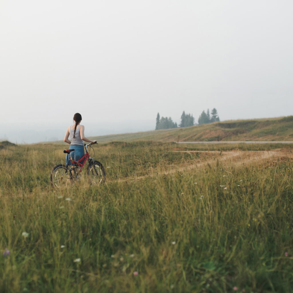 white european young woman in casual clothing going with bicycle on countryside road in hills, view from back in full body size, lifestyles stock photo image